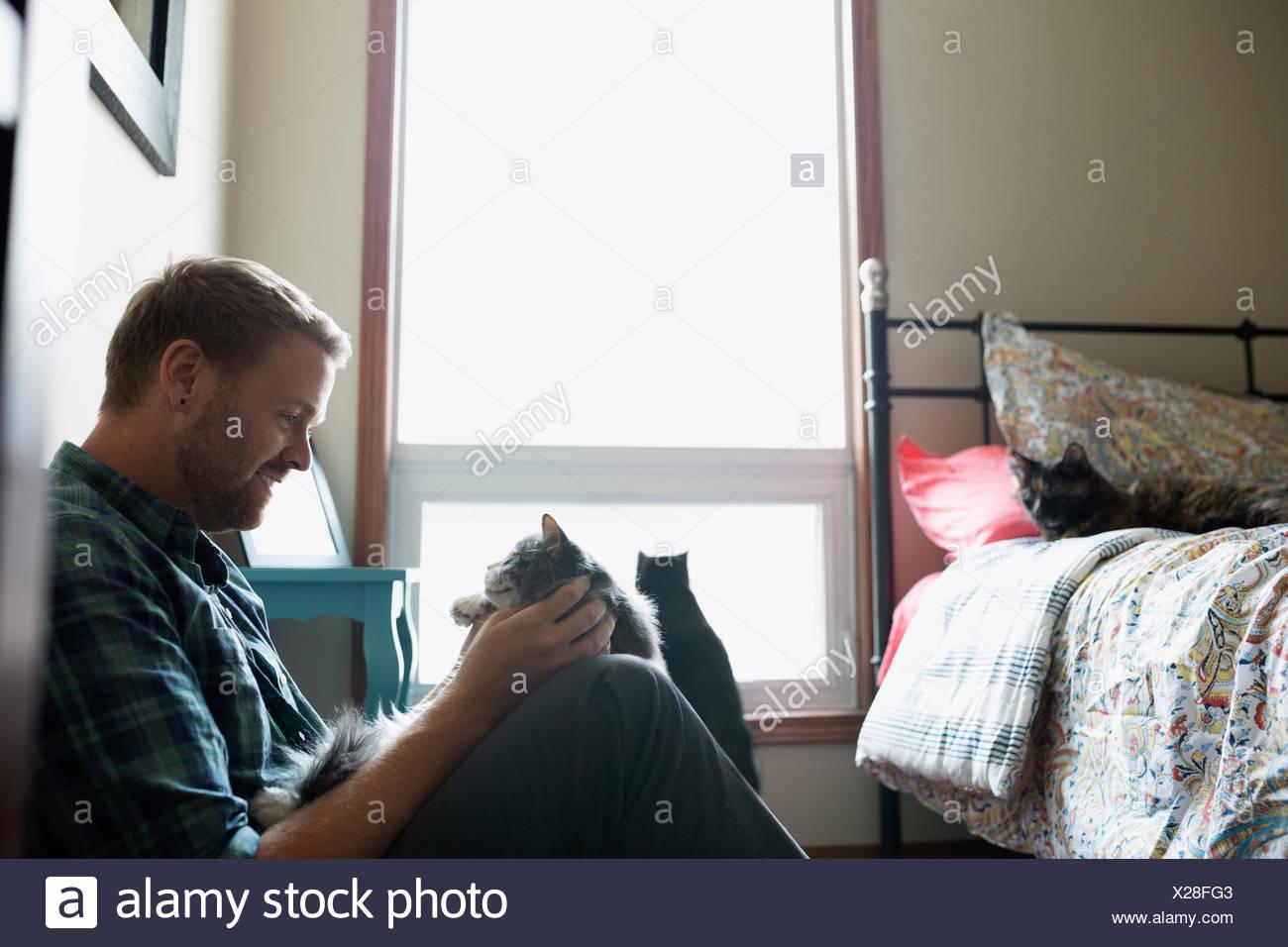 Man petting cat in bedroom - Stock Image
