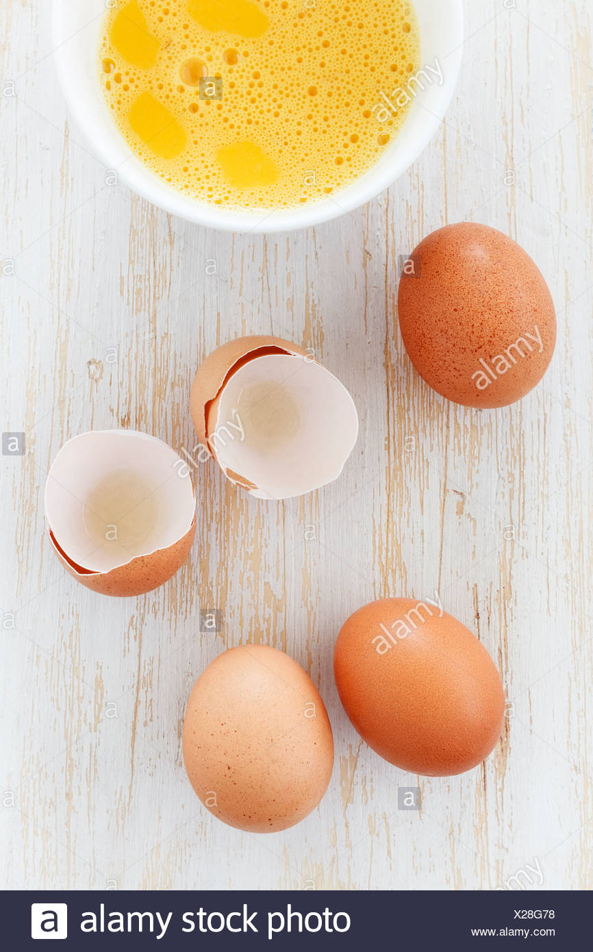 Bowl of breaked open eggs and egg shells on wooden table - Stock Image