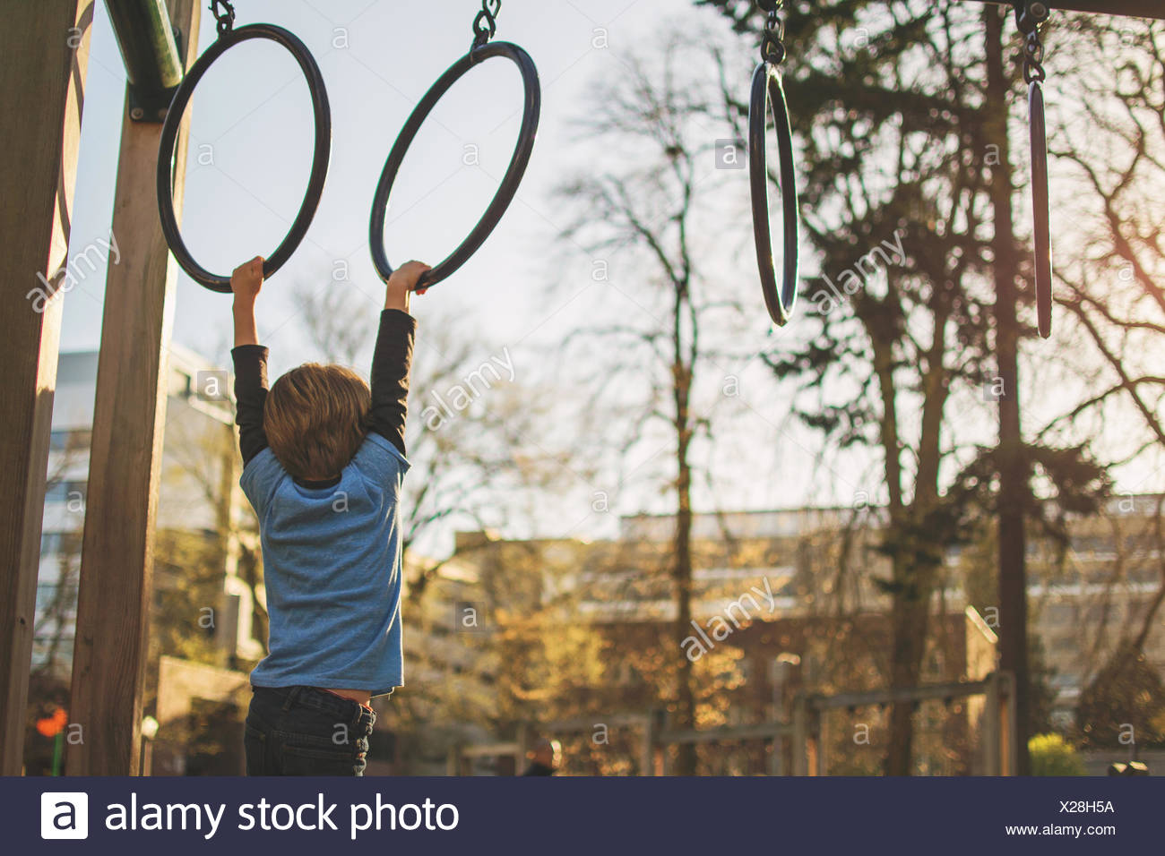 Boy hanging from rings at playground - Stock Image