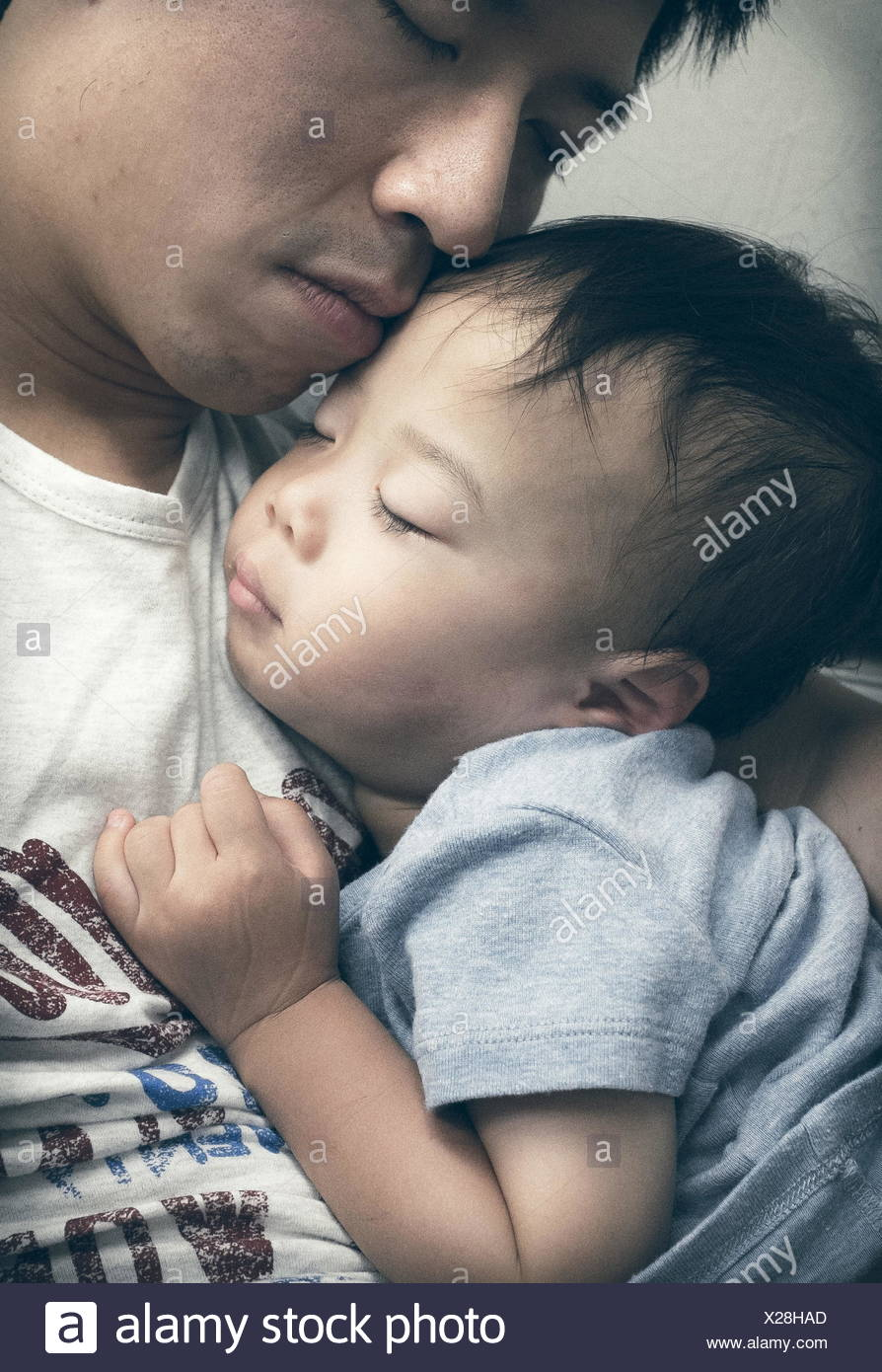 Boy sleeping in father's lap - Stock Image