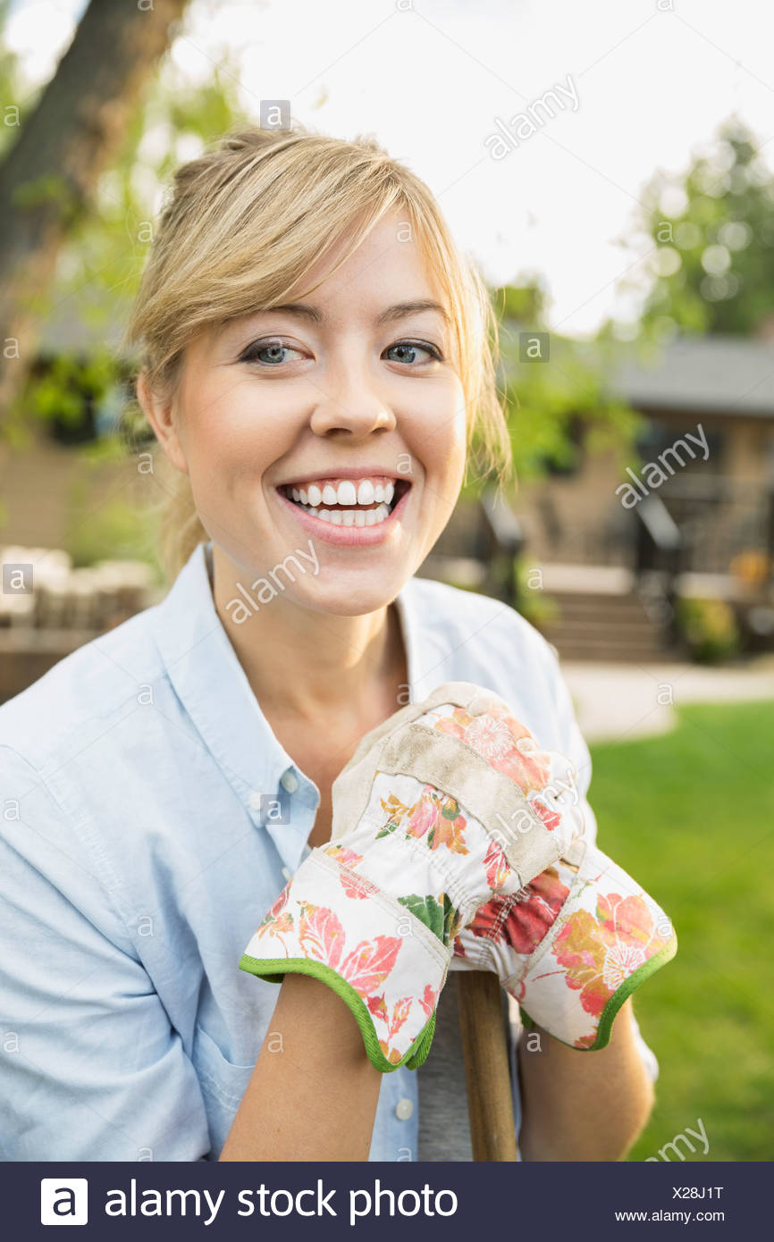 Portrait of enthusiastic woman wearing gardening gloves - Stock Image