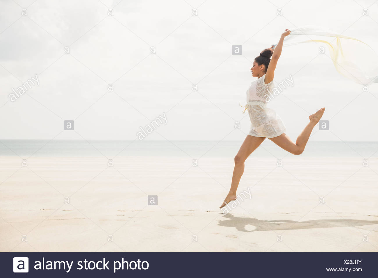 Stylish woman leaping with scarf - Stock Image