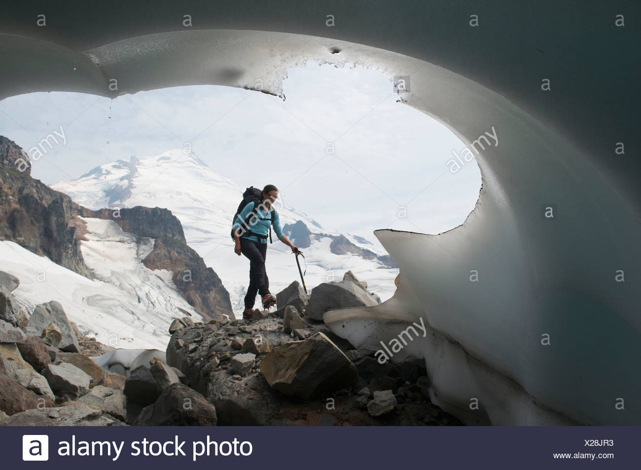 A mountaineering woman passing a glacial terminus, Mount Baker Wilderness, Bellingham, Washington. - Stock Image