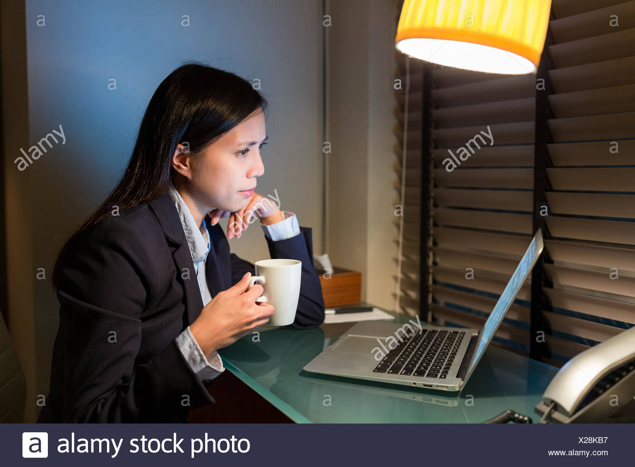 Businesswoman looking at laptop computer and drink of coffee - Stock Image