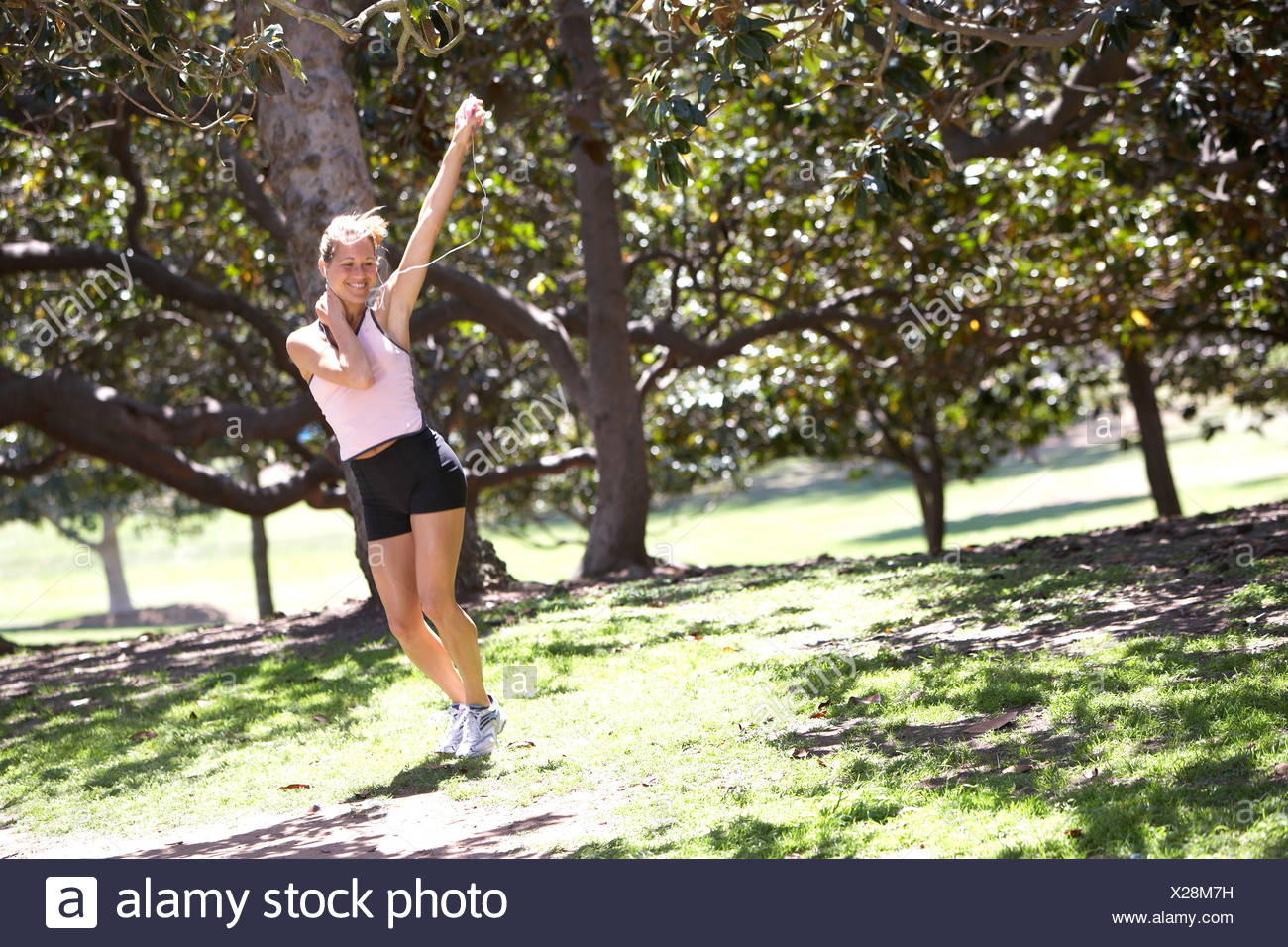 Woman exercising in park listening to MP3 player hand raised smiling trees in background tilt Stock Photo