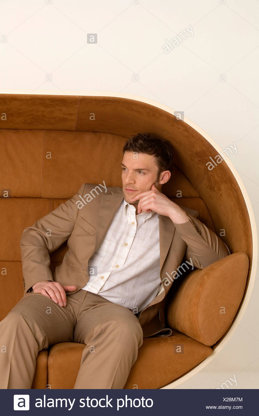 Businessman sitting on sofa, looking away - Stock Image