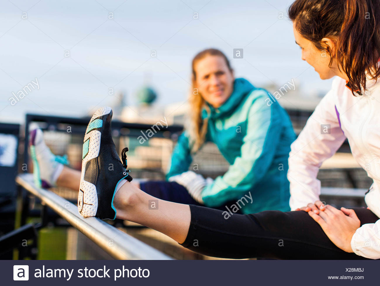 Two female runners stretch their hamstrings after a job near the Puget Sound in Seattle, WA. - Stock Image