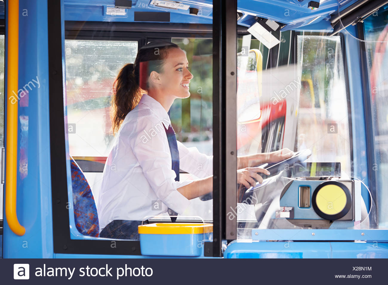 Portrait Of Female Bus Driver Behind Wheel - Stock Image