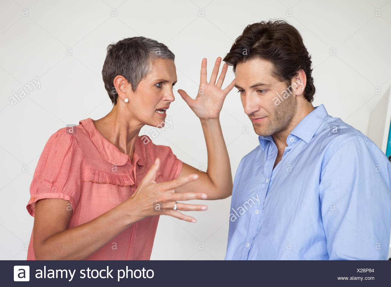 Angry businesswoman shouting at employee - Stock Image