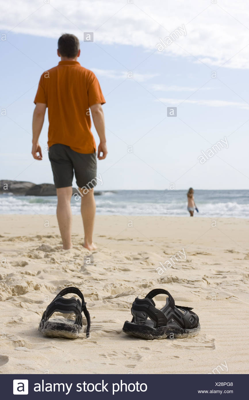 Man barefoot on beach - Stock Image