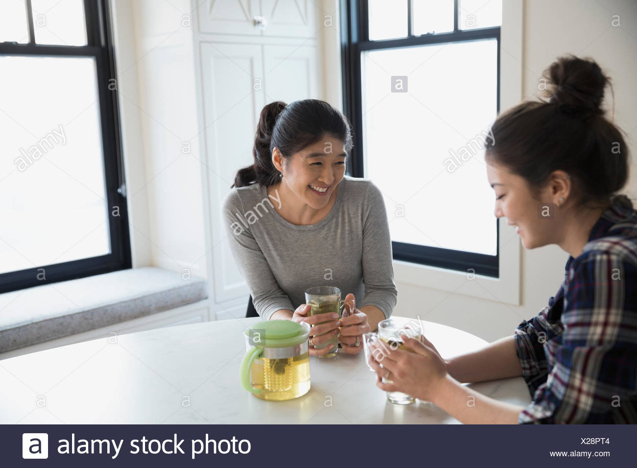 Mother and teenage daughter drinking tea and talking - Stock Image