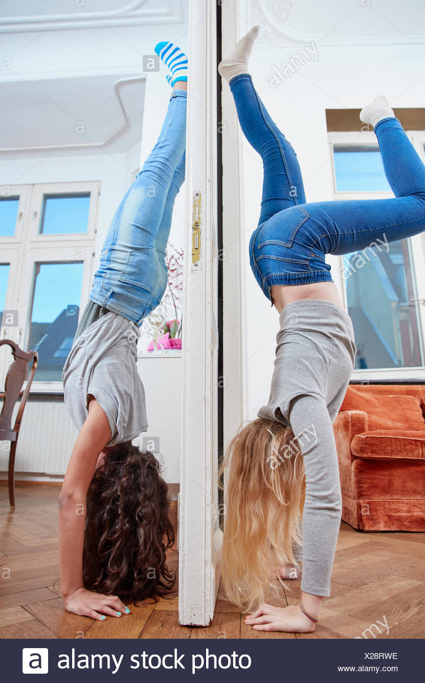 Two girls doing a handstand on opposite sides of a door - Stock Image