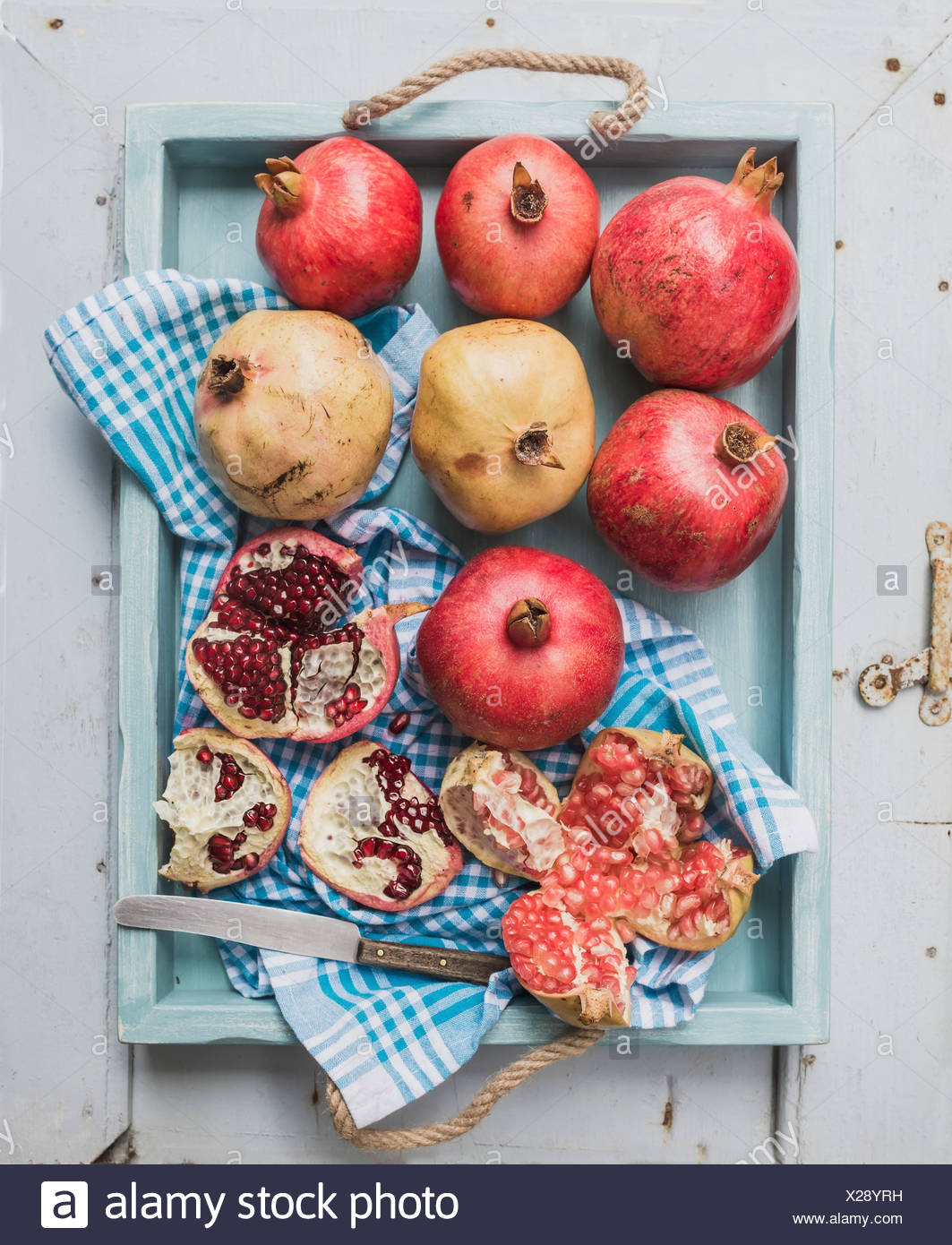 Red and white pomegranates and knife on kitchen towel in blue tray over light painted wooden backdrop, top view - Stock Image