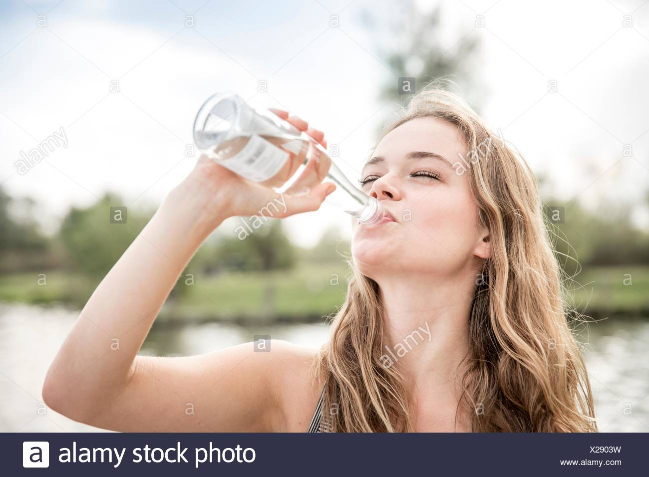 Young woman drinking water from bottle, outdoors - Stock Image
