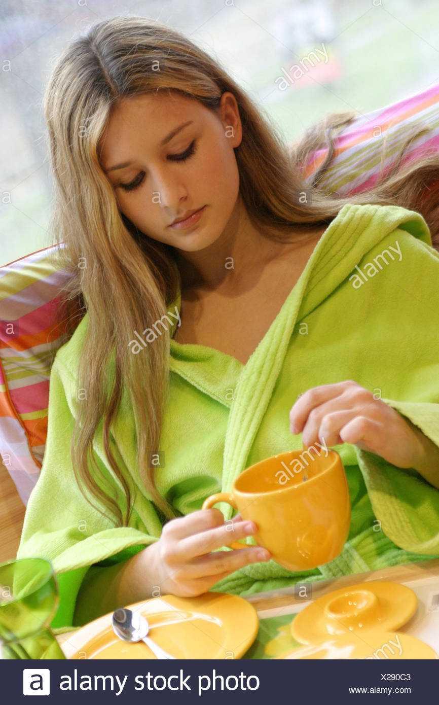 blond woman wearing morning coat stirring in cup. - Stock Image
