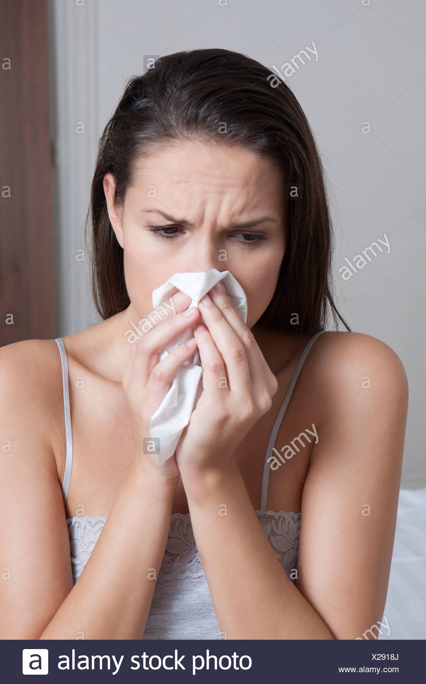 Woman blowing her nose on bed - Stock Image