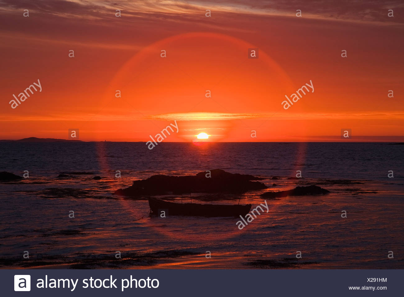 Sunset over mannin bay in a circular glare;County galway ireland - Stock Image