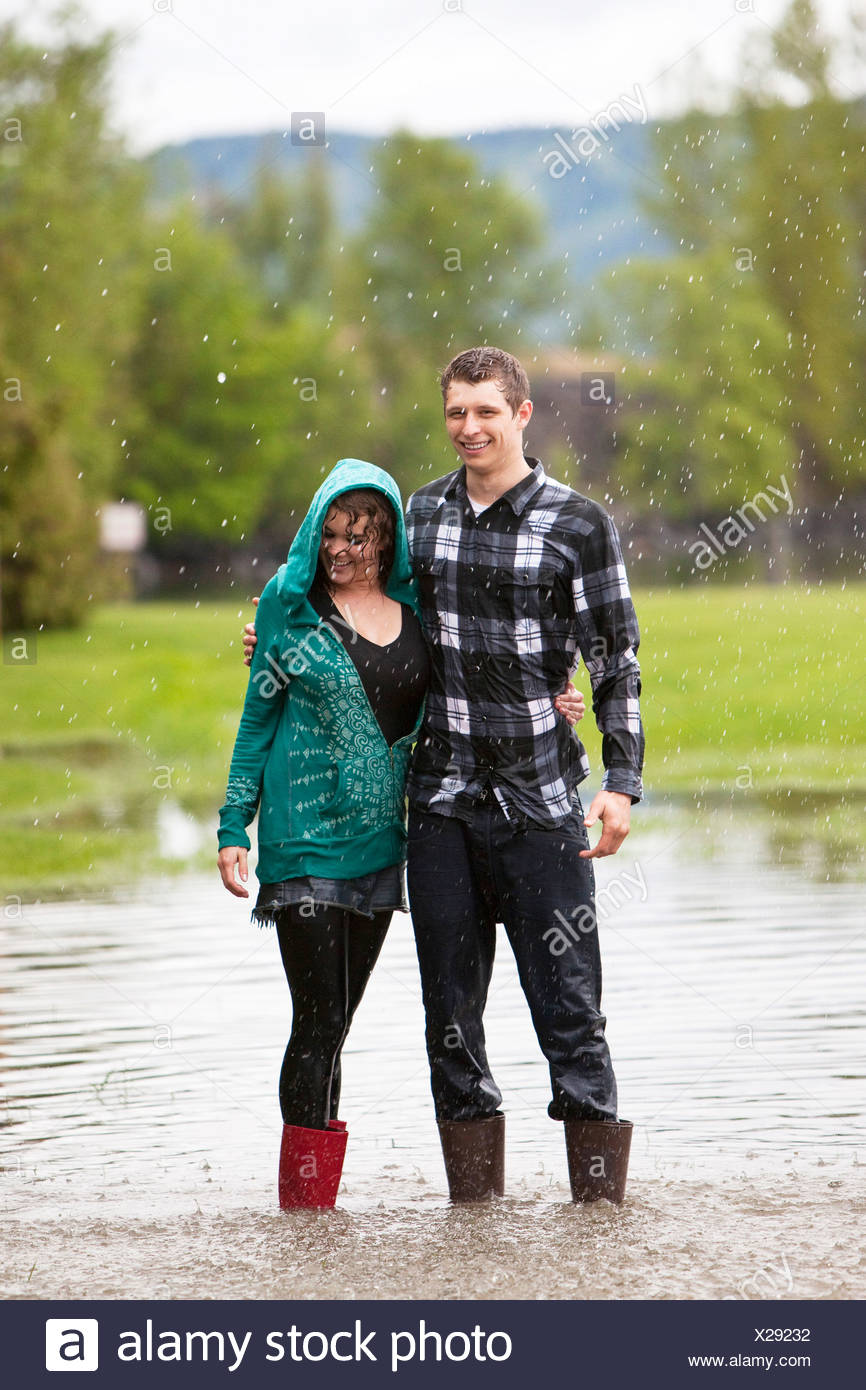 A young couple stands in a large puddle after having a water fight. - Stock Image