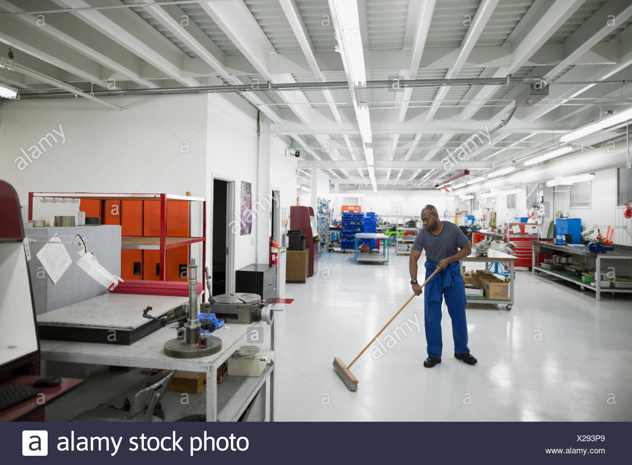 Helicopter mechanic sweeping workshop floor - Stock Image