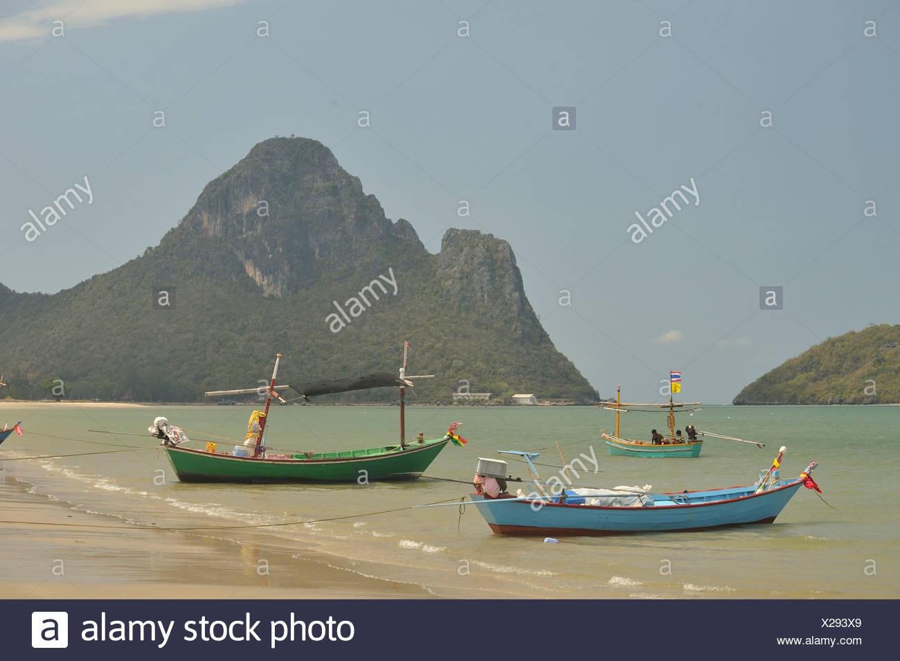 beached fishing boats in Prachuap Kiri Khan Harbour, Gulf of Thailand, Thailand - Stock Image