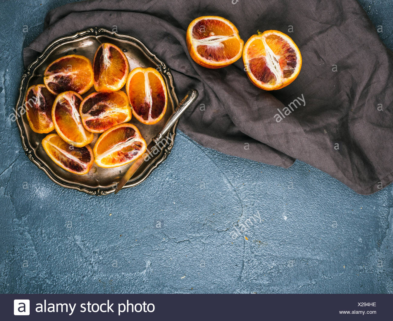 Bloody red sicilian oranges cut into quarters in vintage metal plate over concrete textured background, top view - Stock Image