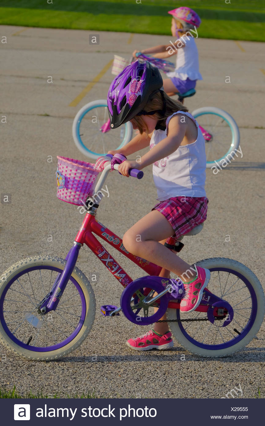 Two girls practice their two wheeled bike riding skills in a parking lot. - Stock Image