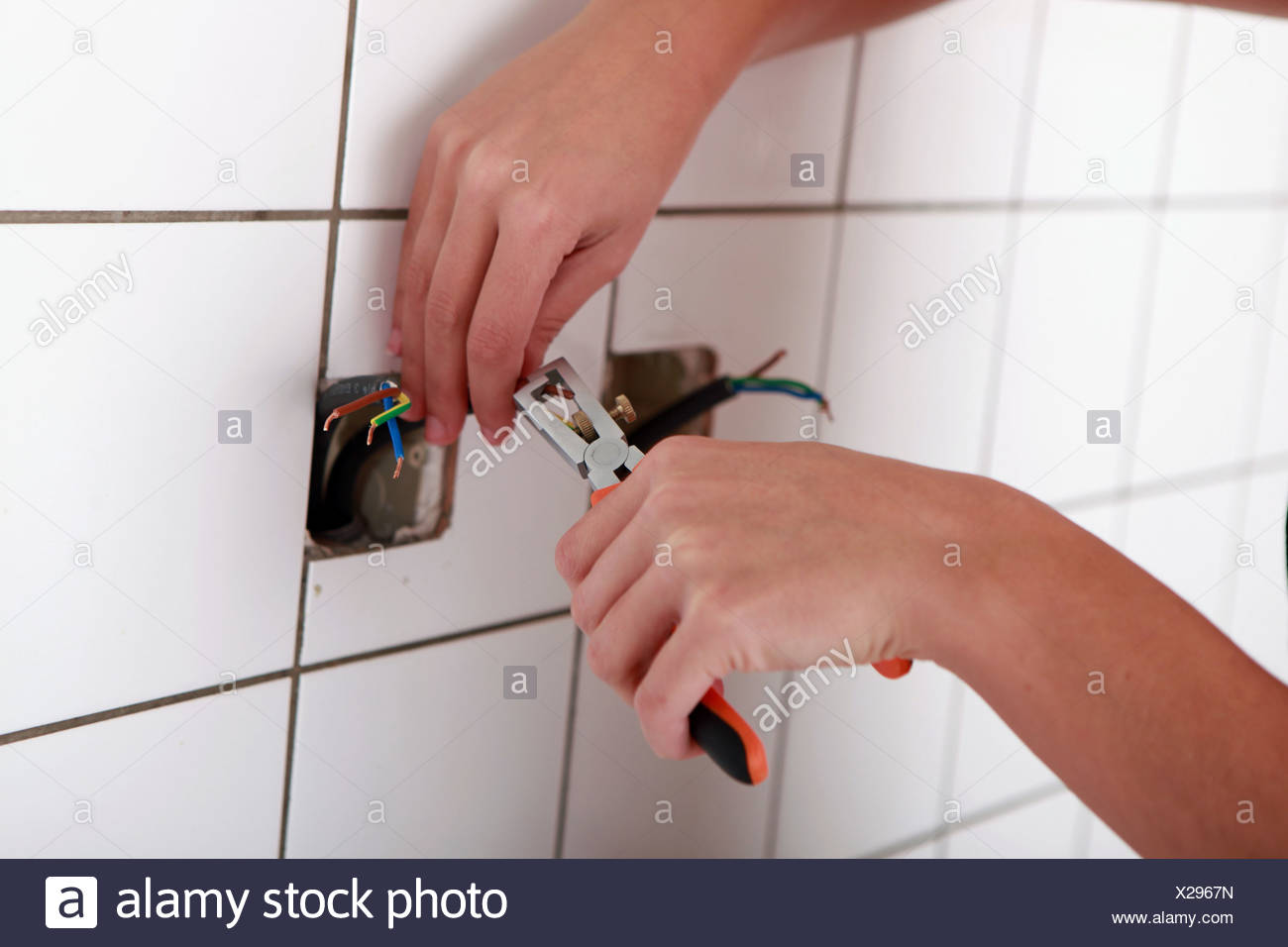 close-up of someone using a stripping plier for an electrical outlet - Stock Image