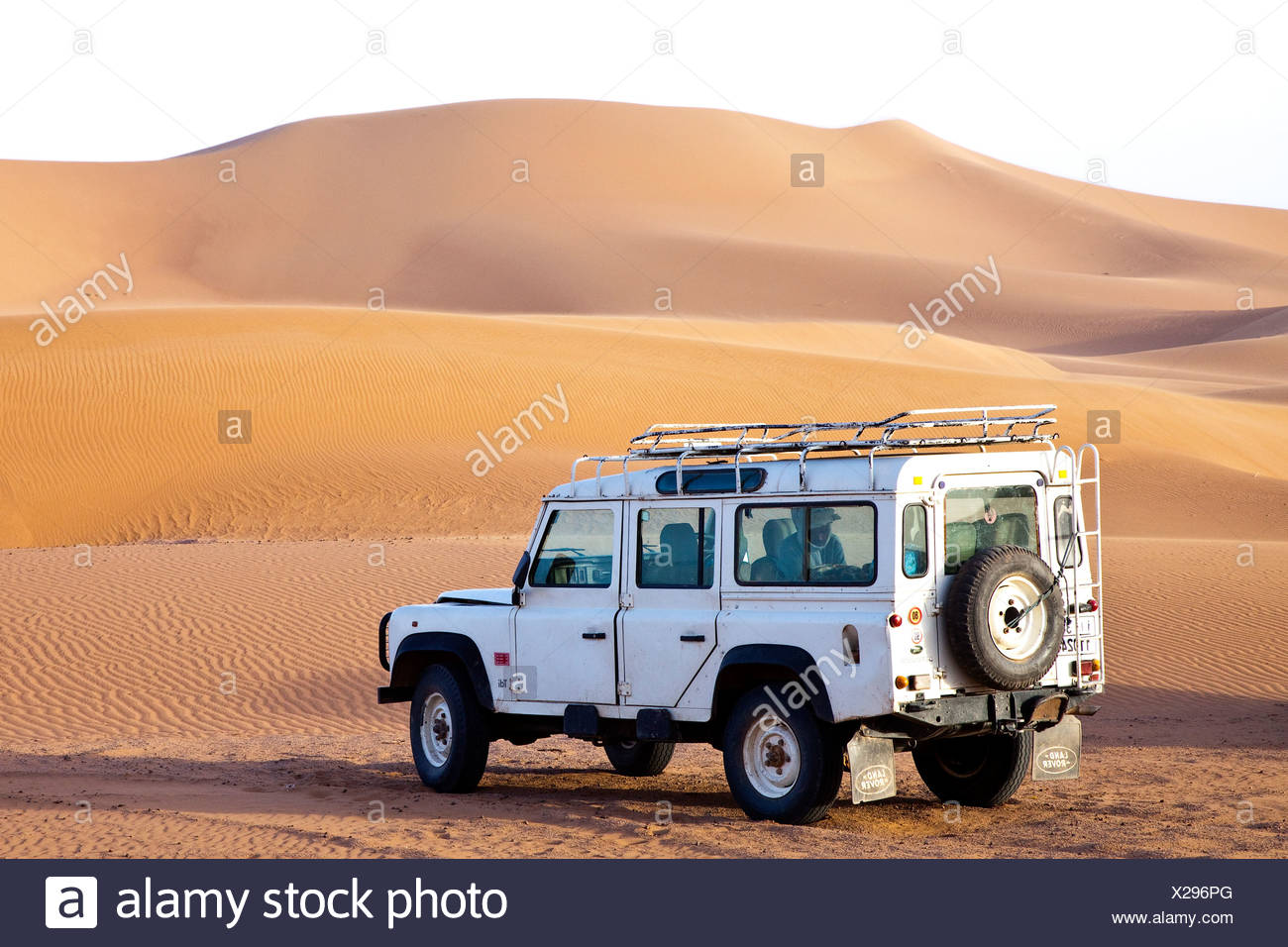 All-terrain vehicle, Land Rover Defender, sand dunes of Erg Chegaga, Sahara Desert near Mhamid, Morocco, Africa - Stock Image