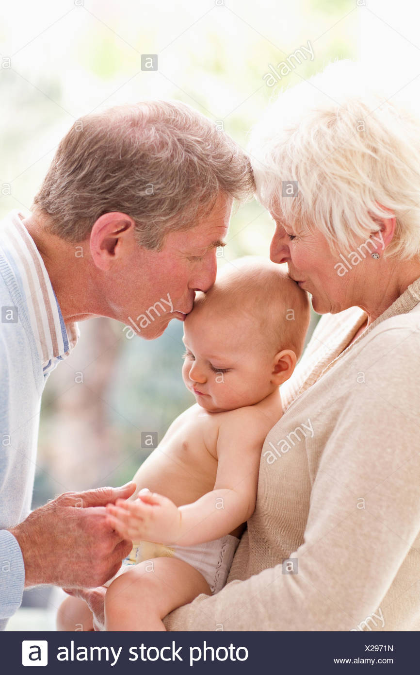 Grandparents holding and kissing baby - Stock Image