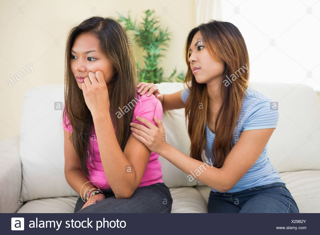 Upset woman sitting on a couch being consoled by her sister - Stock Image
