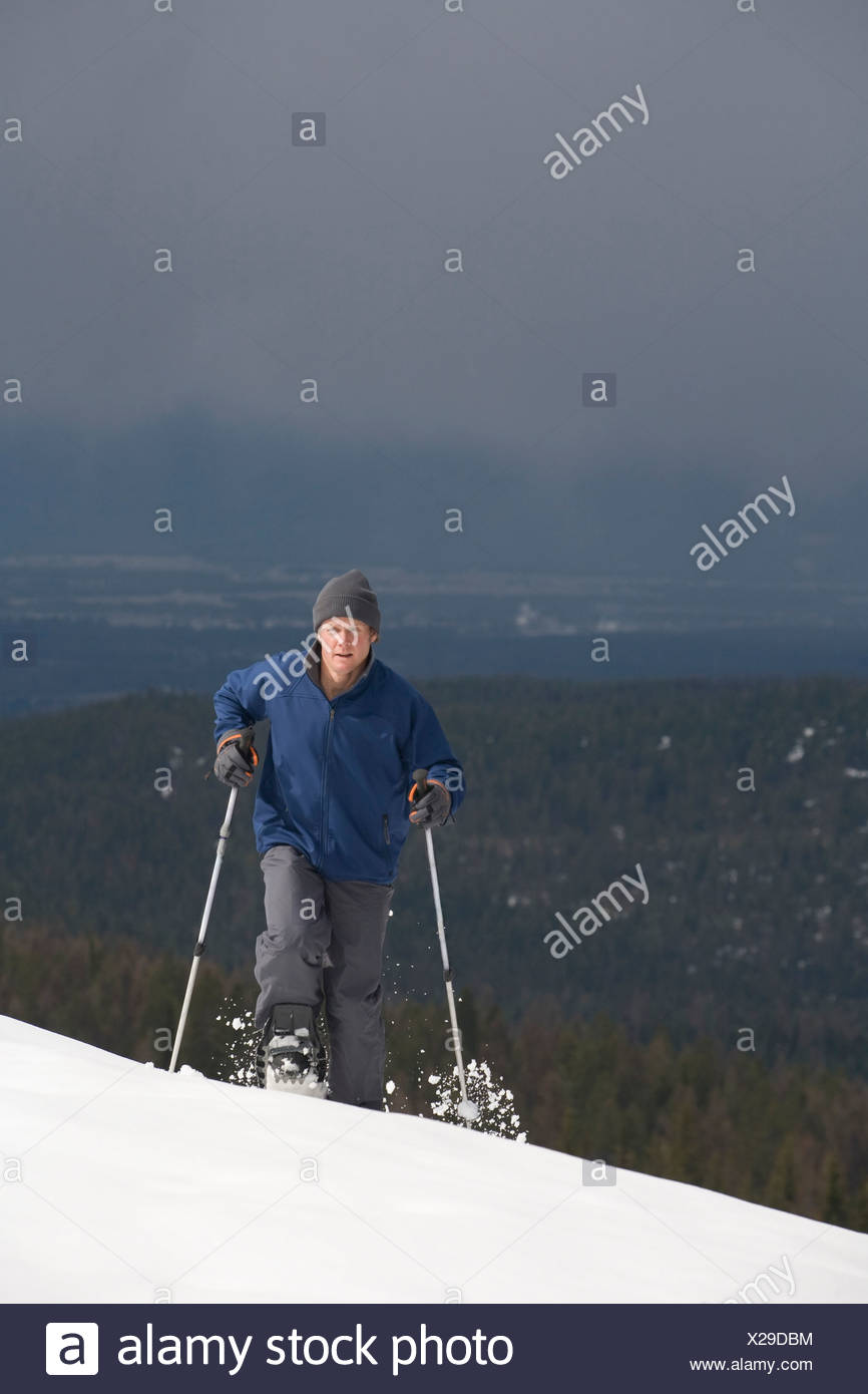 A solo male snowshoer makes his way up a mountain. - Stock Image