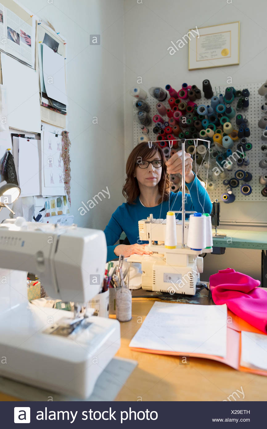 Dressmaker using sewing machine at workbench - Stock Image