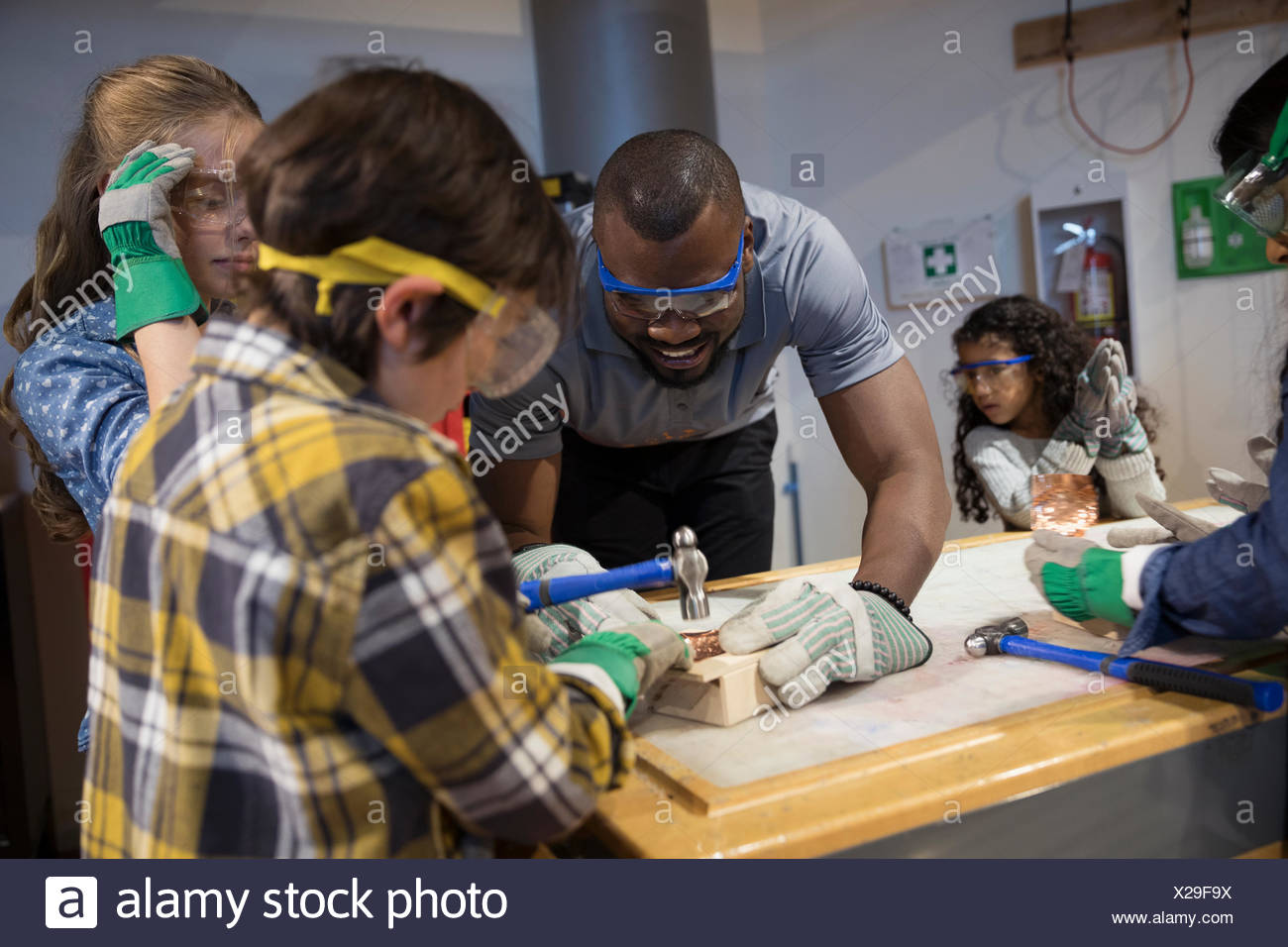 Scientist and children hammering wood in science center - Stock Image