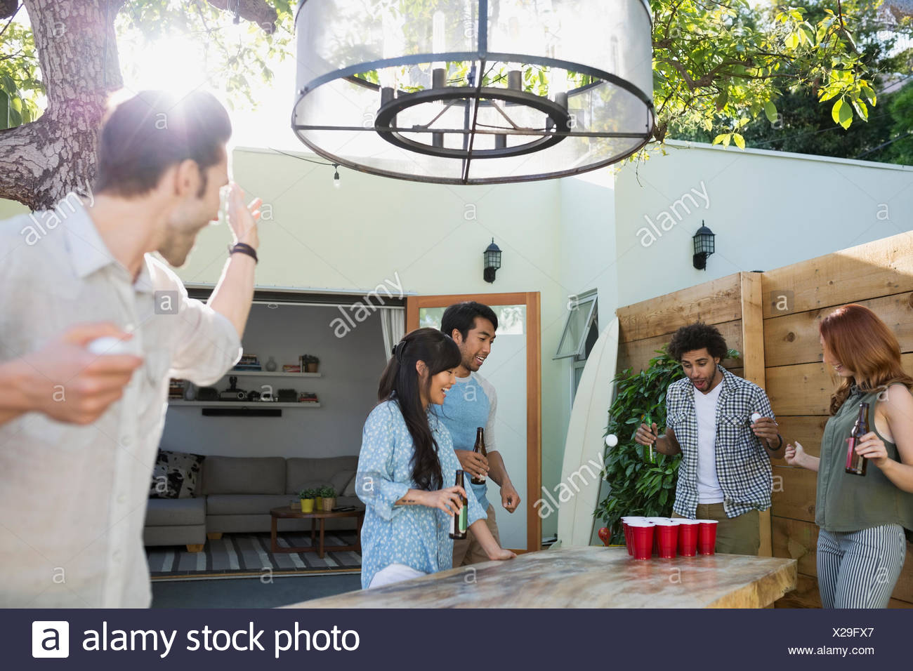Friends playing beer pong on sunny patio - Stock Image