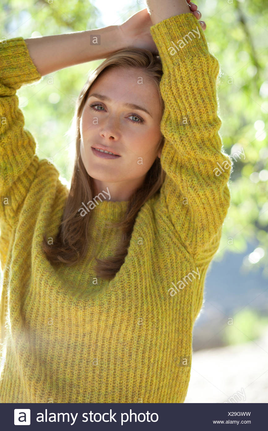 Portrait of yearning young woman wearing knit pullover - Stock Image