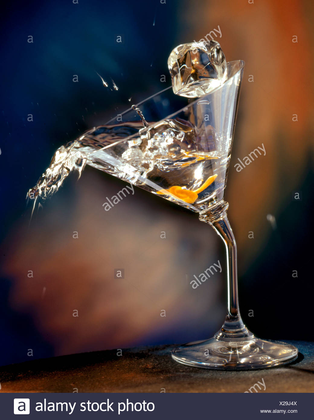 Vodka Martini Spilling From a Bent Martini Glass with Ice Cube - Stock Image