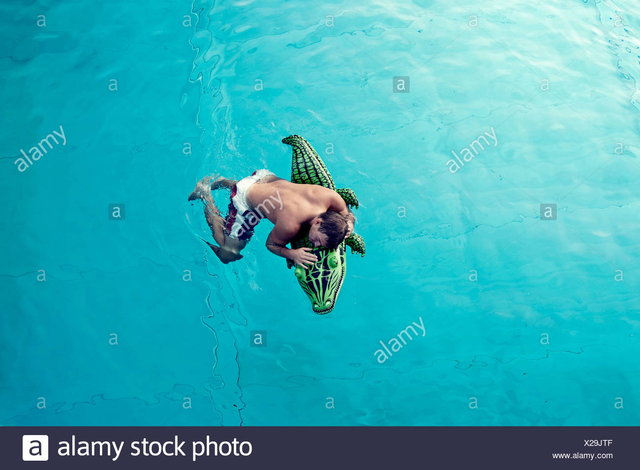 Young man with swim toy floating in water, view from above - Stock Image