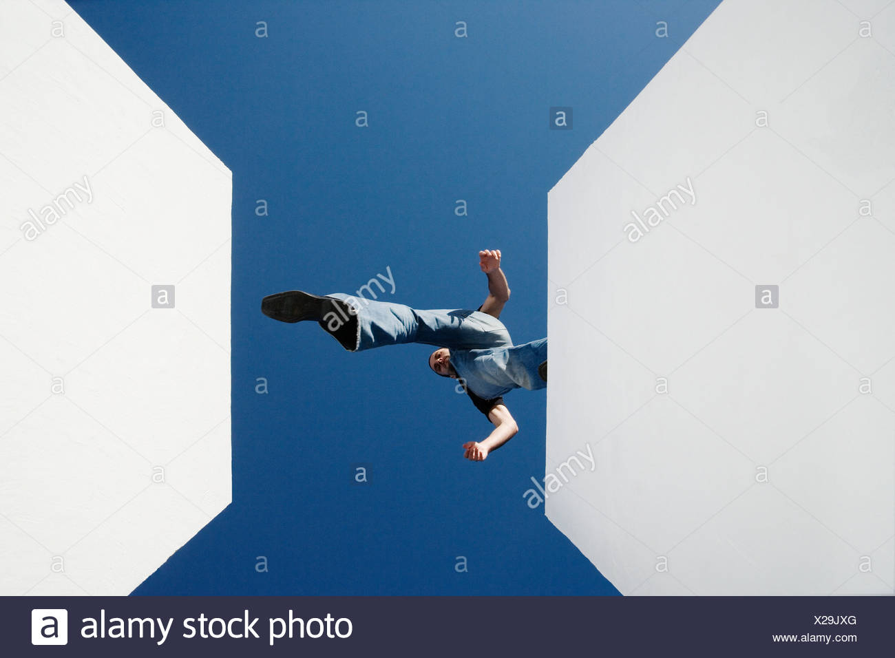 Low angle view of man walking across high gap outdoors - Stock Image