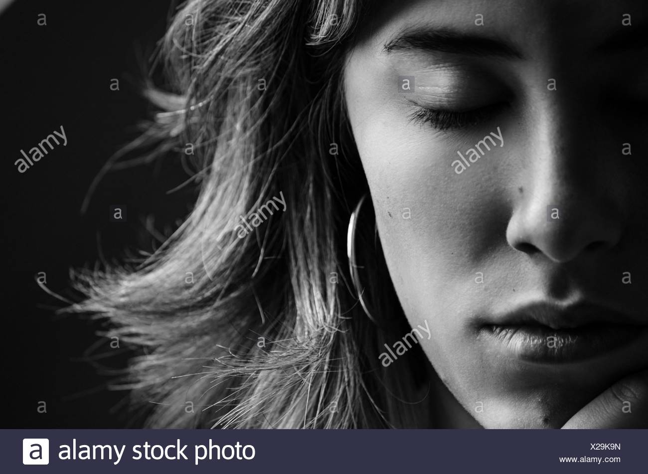 Portrait of young woman with her eyes closed - Stock Image
