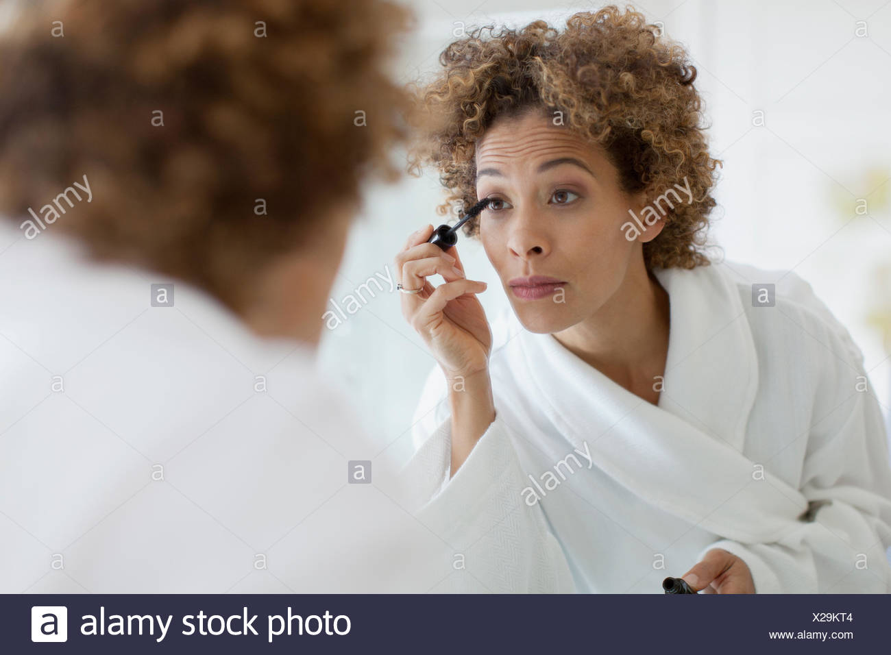 Woman applying make-up in mirror. - Stock Image