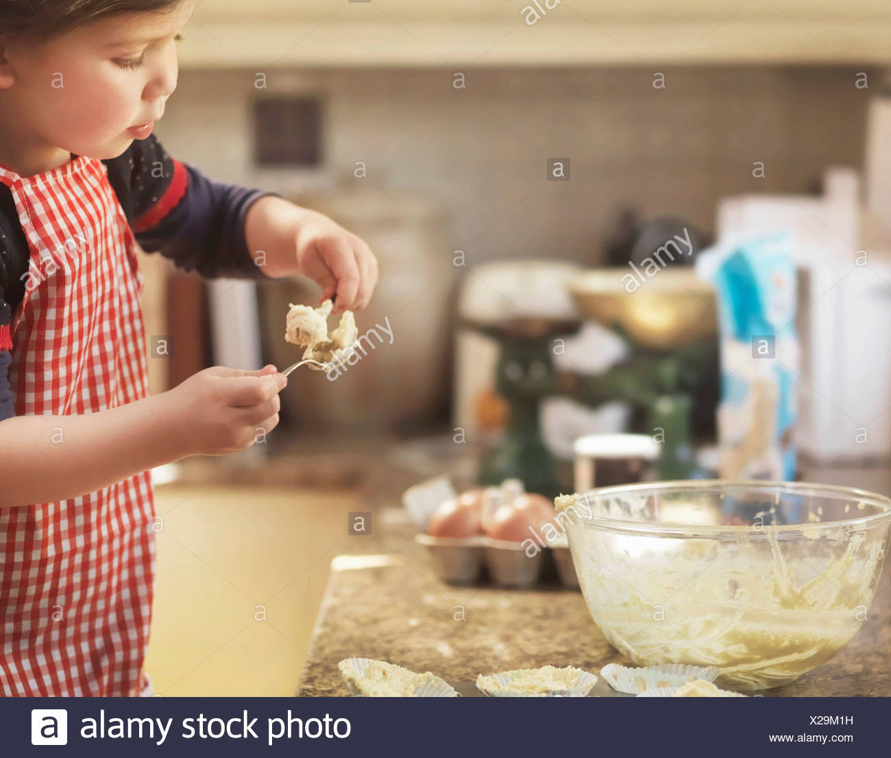 Child holding spoon with cake mix Stock Photo