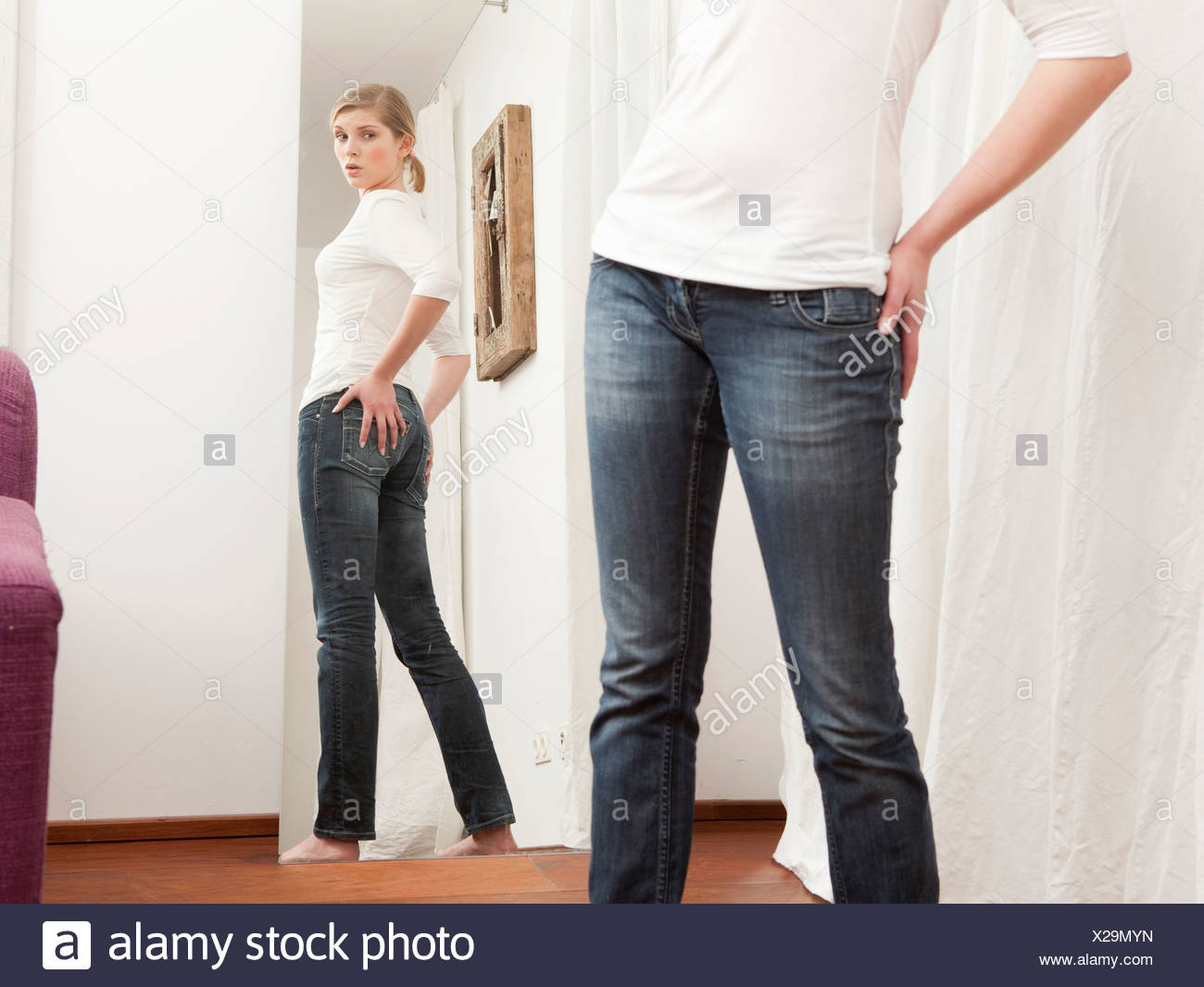 Woman checking her body in the mirror. - Stock Image