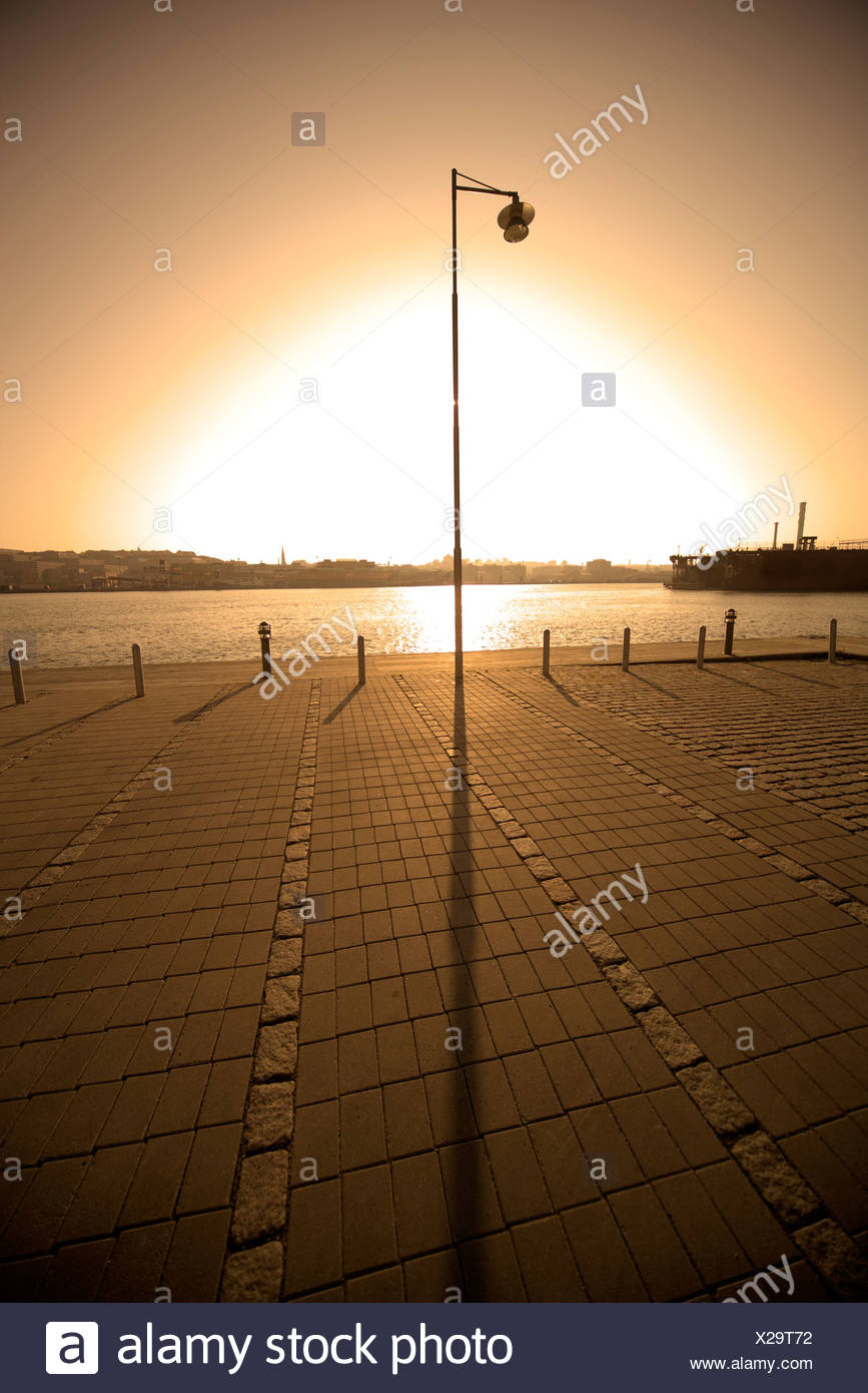 Lone streetlight on empty quay with sunlight in the background - Stock Image