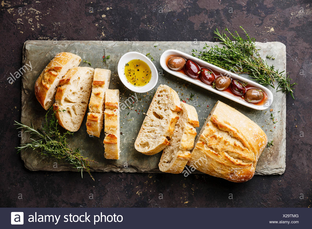 Fresh Ciabatta bread cut in slices on stone slate board with olives, oil and herbs on dark background - Stock Image