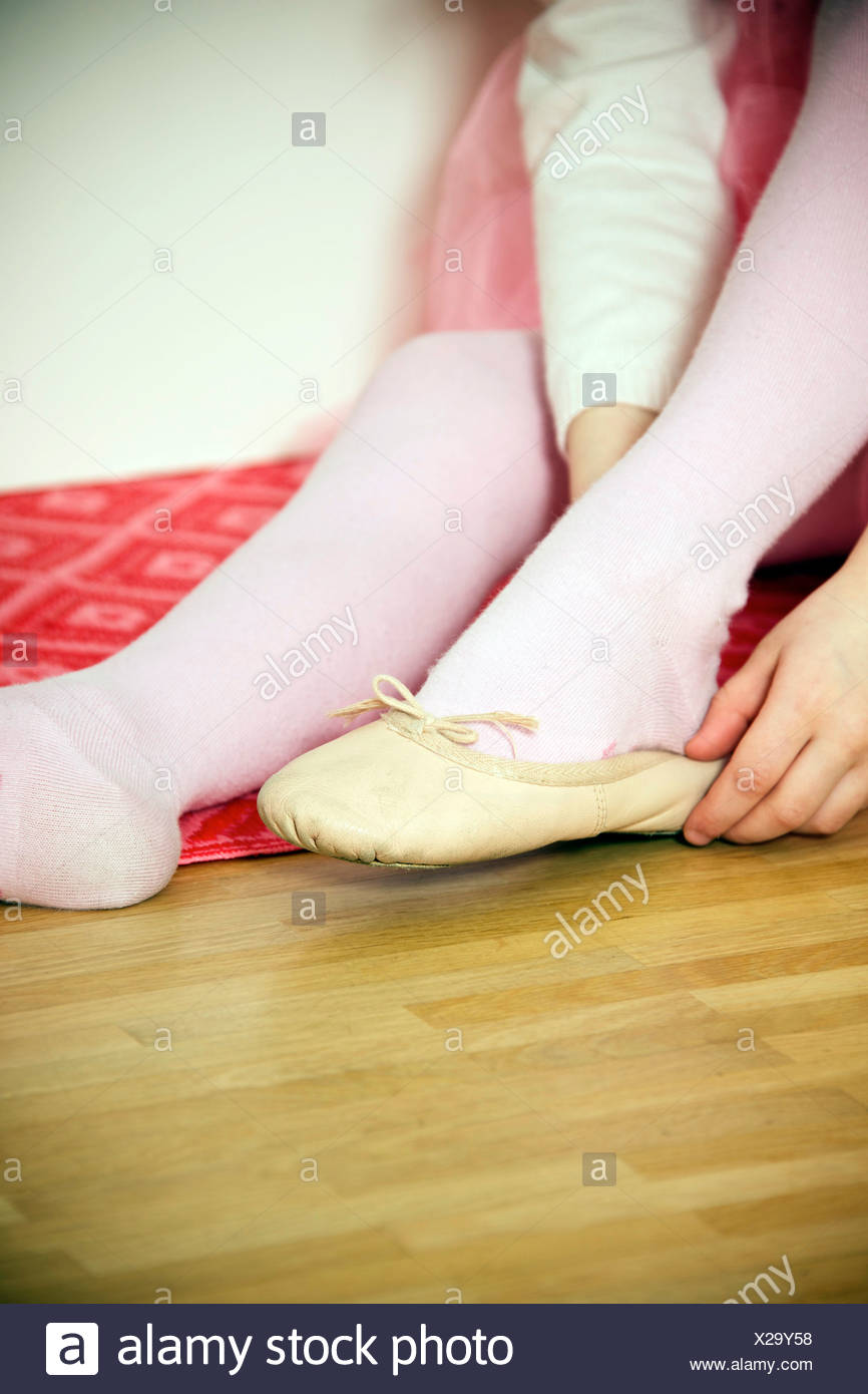 Girl putting on ballet shoe - Stock Image
