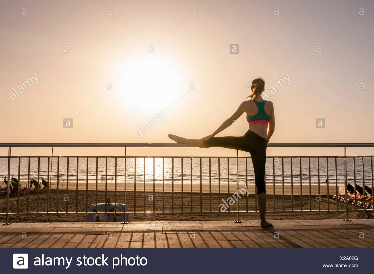 Rear view of mid adult woman on coastal path leg raised on railing looking away at view Stock Photo