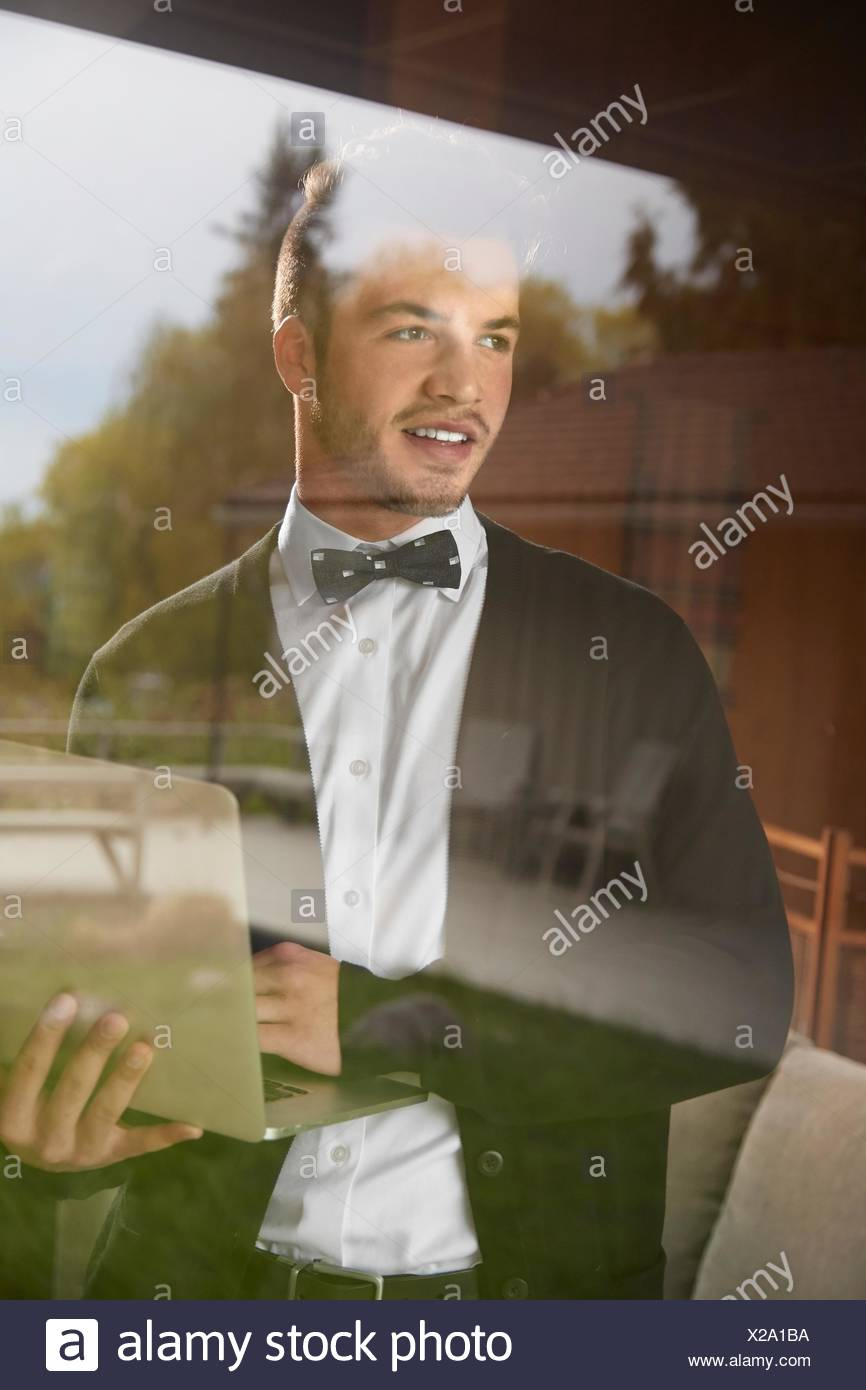 Shot through window of man standing looking out at the view holding laptop - Stock Image