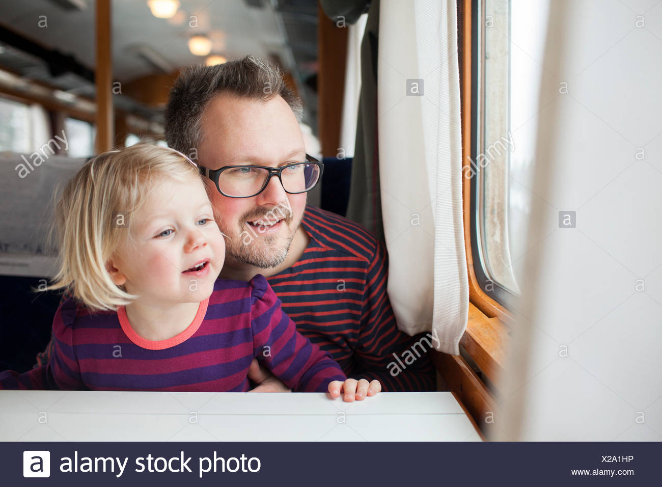 Sweden, Father and daughter (2-3) traveling by train - Stock Image