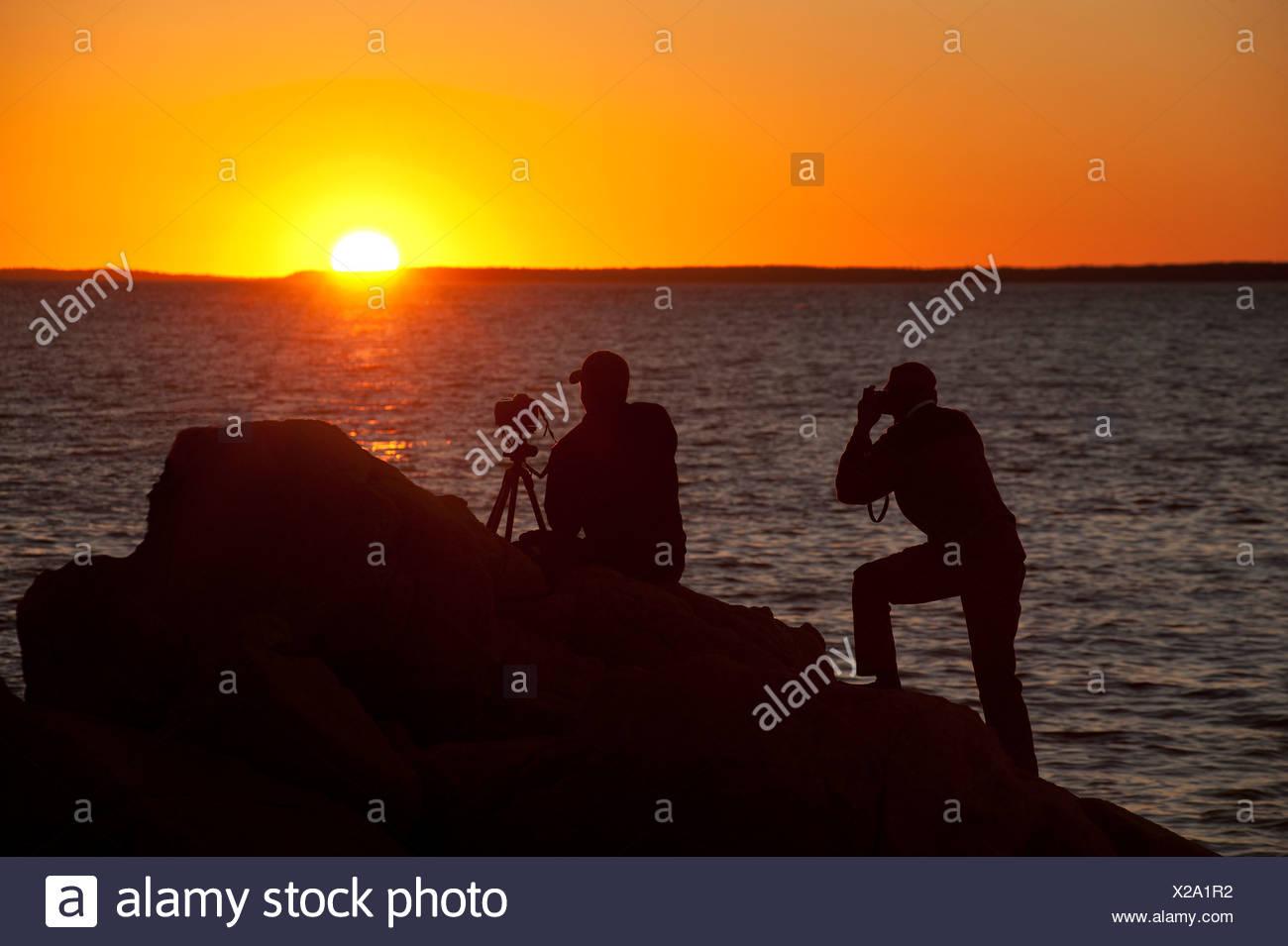 Photographers shooting coastal sunset. - Stock Image