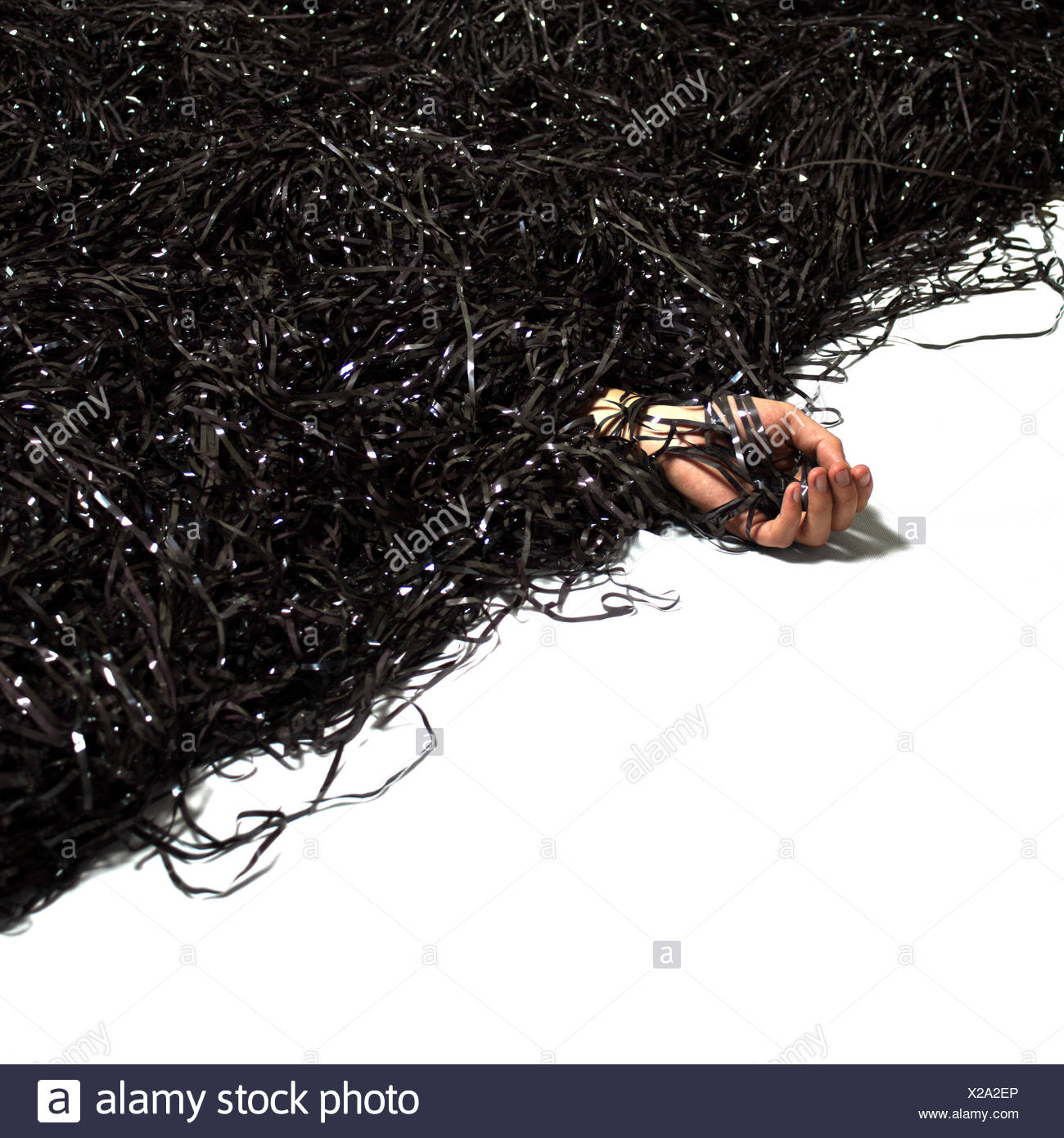 Man's hand emerging from pile of recording tape - Stock Image